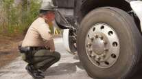 An officer performs a roadside inspection