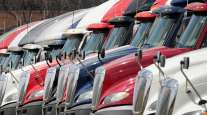 International trucks sit parked in a lot outside a Navistar facility.