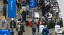 Travelers wearing protective masks check in at San Francisco International Airport on Nov. 24.