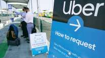 California travelers request an Uber ride. (Damian Dovarganes/Associated Press)