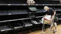 A woman wearing a face mask near empty fruit and veg shelves in Cardiff, Wales