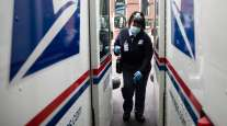 A USPS carrier gets into her truck to deliver mail in Philadelphia in May.