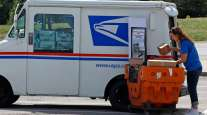 A postal worker loads a delivery vehicle at the post office in Cranberry Township, Pa.