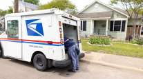 A postal service worker works out of the back of his truck