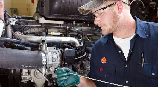 Shell technician checks engine oil