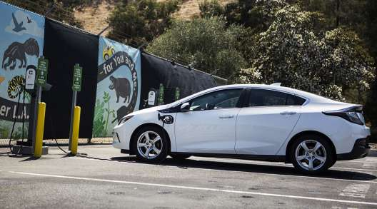 A ClipperCreek Inc. charging plug is connected to a GM Chevrolet Volt electric vehicle at a charging station in Los Angeles