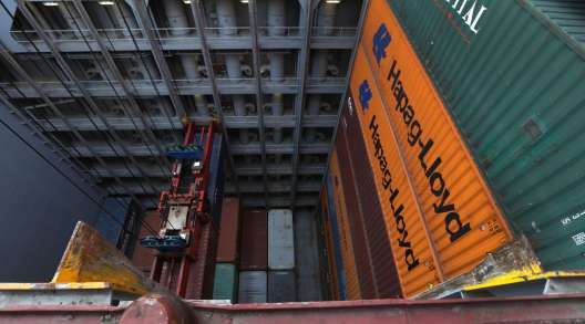 A pair of shipping containers hang from a ship-to-shore crane while a Hapag-Lloyd ship is unloaded.