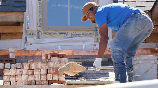A mason shovels a cement mixture as he prepares to lay down bricks on the exterior wall of a new house in Flowood, Miss.