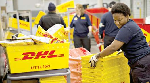 Employees sort crates of packages at a DHL facility in Chicago. (Daniel Acker/Bloomberg News)