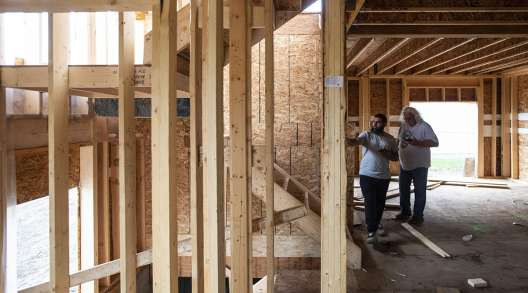 Workers inspect a home under construction by Akash Homes in Edmonton, Alberta, Canada.