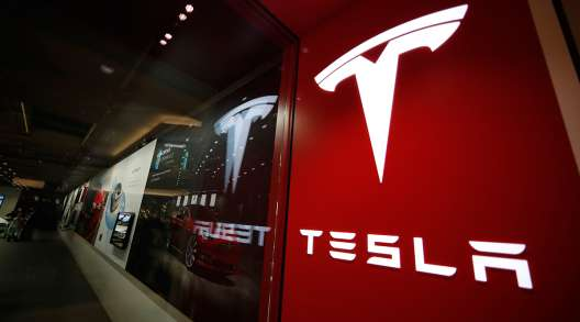 A sign bearing the company logo outside a Tesla store in Cherry Creek Mall in Denver