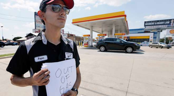 "Gas station employee holds ""out of gas"" sign"