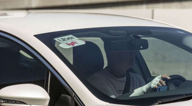 Lyft and Uber logos are displayed on the windshield of a vehicle at LAX.
