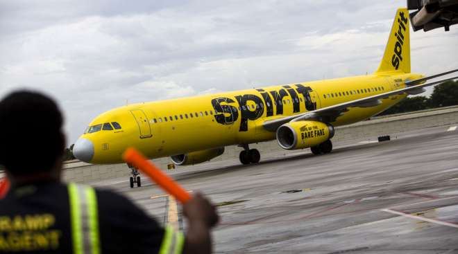 An aircraft marshal guides a Spirit Airlines plane on the tarmac.