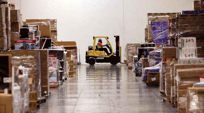 A worker drives a forklift past merchandise at the Amazon.com Phoenix Fulfillment Center in Goodyear, Ariz.