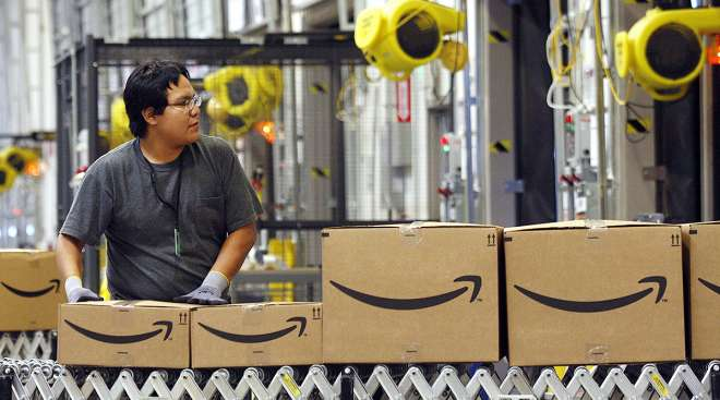 An Amazon worker watches as boxed merchandise moves along a conveyor be
