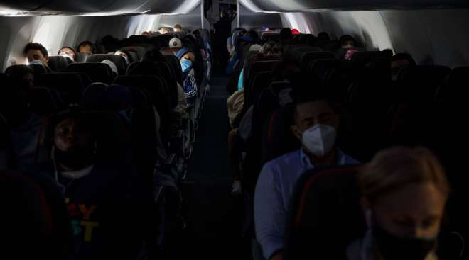 Passengers sit on an American Airlines flight departing from Los Angeles International Airport