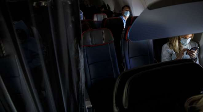 Passengers wear protective masks on an American Airlines flight