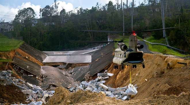 A U.S. Army helicopter transports material to repair the Guajataca Dam