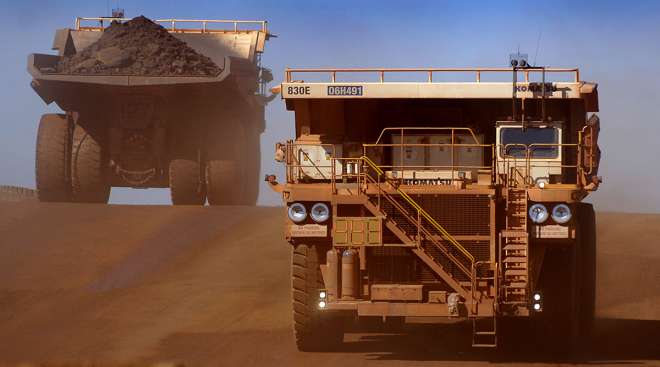 Heavy earth moving trucks at the Tom Price iron ore mine, operated by Rio Tinto Group, are lit up by the afternoon sun in Pilbara, north Western Australia.