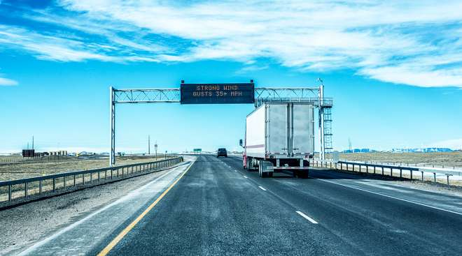 A tractor-trailer passes under an electronic road sign warning of strong wind gusts on Interstate 80 between Cheyenne and Laramie, Wyo.