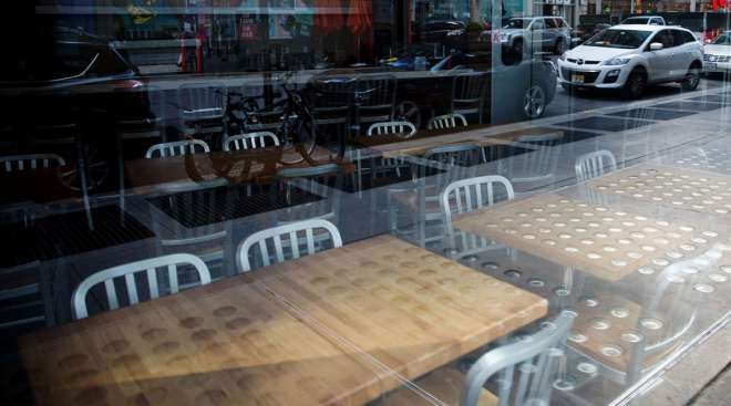 Chairs and tables sit inside a closed restaurant in Times Square in New York on April 21.
