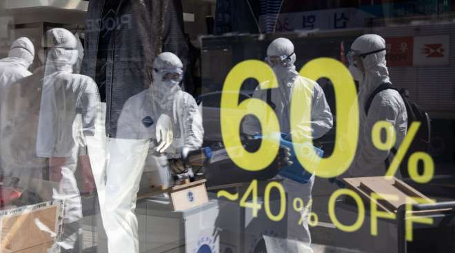 Workers wearing protective suits are reflected in a glass window of a clothing store in Seoul, South Korea, on Feb. 27.