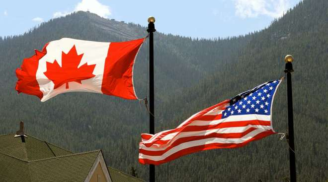 Canada, USA flags blowing in wind
