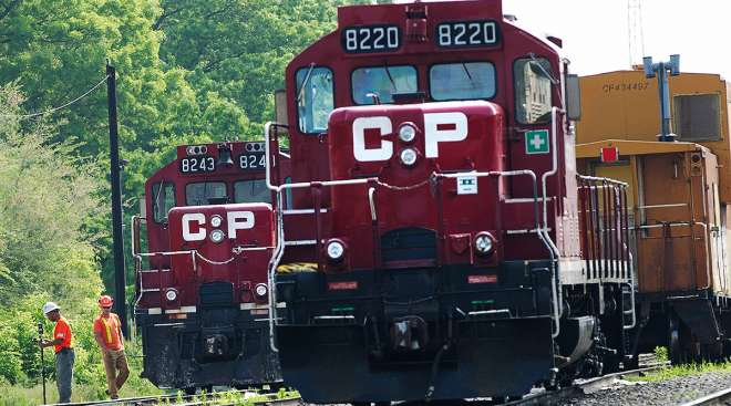 Surveyors work next to Canadian Pacific Rail trains parked on tracks in Toronto