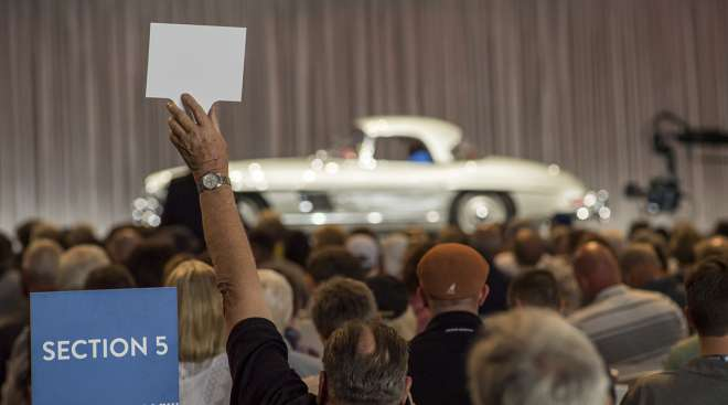 A bidder makes a bid on a 1957 Mercedes-Benz AG 300 SL Roadster during the Gooding and Company auction during the  Pebble Beach Concours d'Elegance in Pebble Beach, Calif.