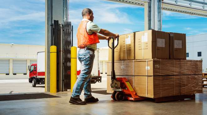 A worker pushes a hydraulic hand pallet truck at a warehouse