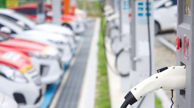 Row of electric cars at charging stations