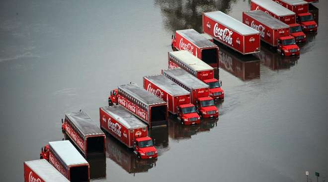 Coca-Cola delivery semi-trailer trucks sit in floodwater in Lumberton, Texas