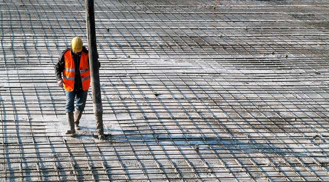 Worker pumping concrete at construction site