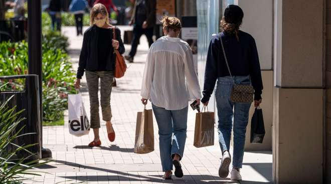 Shoppers wearing protective masks carry bags in Walnut Creek, Calif., in April. (Bloomberg News)