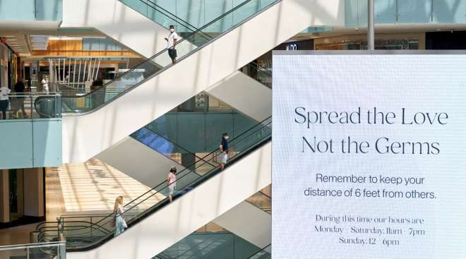 """A """"Spread The Love Not The Germs"""" sign is displayed at a mall in Dallas."""