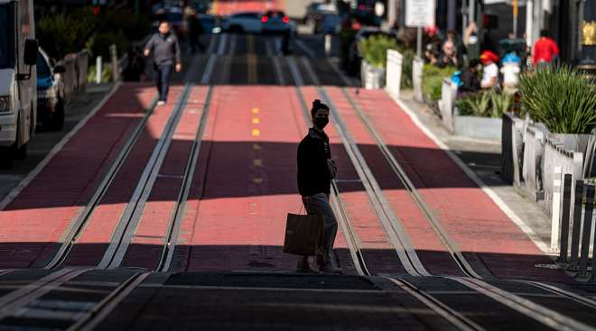 A pedestrian wearing a protective mask carries a shopping bag in San Francisco. (David Paul Morris/Bloomberg News)
