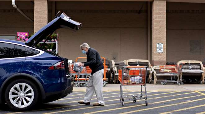A customer wears a protective mask while loading purchases from a Home Depot store in Reston, Virginia, on May 21.