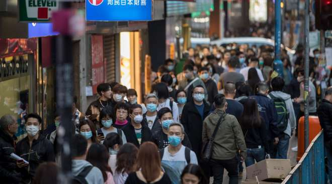 People wearing masks walk on a street in the Kwun Tong district of Hong Kong, China, on Jan. 23.