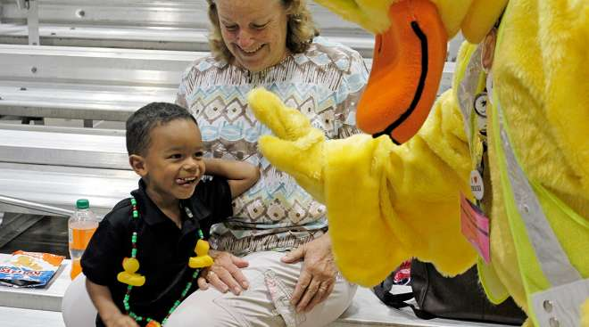 The duck mascot high-fives a young fan