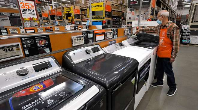 Home Depot worker Javad Memarzadeh of Needham, Mass., dusts washing machines at a Home Depot location in Boston.