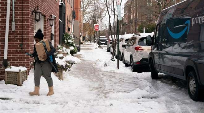 An Amazon delivery driver carries a package through the snow in Philadelphia