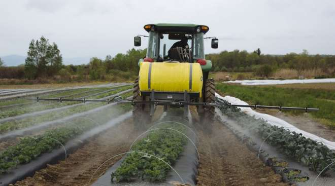 A worker rides a tractor while spraying organic pesticide on crops at a farm in Hudson, N.Y.