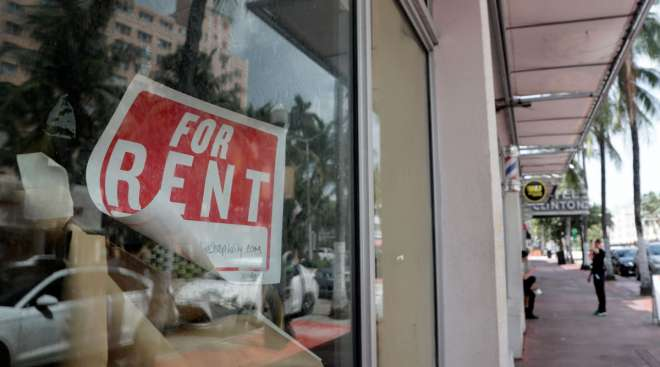 """A """"For Rent"""" sign hangs on a closed shop in Miami Beach, Fla., on July 13."""