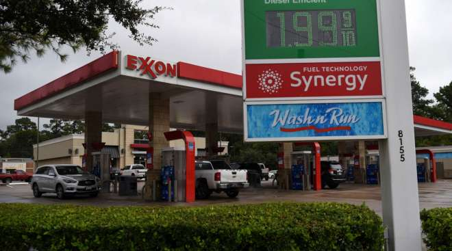 Vehicles refuel at an Exxon Mobil Corp. gas station in Houston on Oct. 28. (Callaghan O'Hare/Bloomberg News)