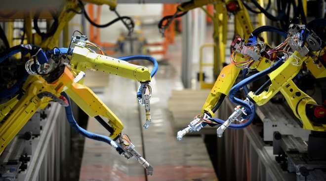 Robotic painting arms are tested in the underbody sealing and coating area of the Chrysler Group Assembly Plant in Sterling Heights, Mich.
