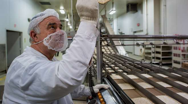 A Mashgiach, a Jew who supervises the kashrut status of a kosher establishment, inspects Passover matzo after it comes out of an oven at the Manischewitz Co. factory in Newark, New Jersey, U.S., on Thursday, Feb. 20, 2014.