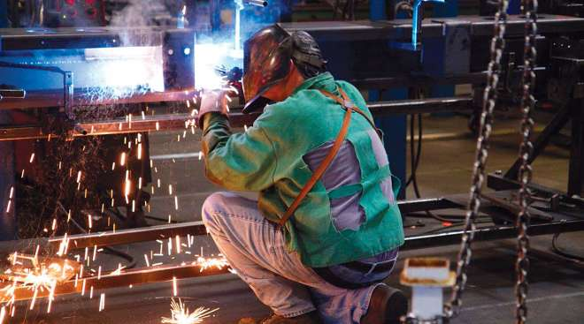 A worker prepares parts at a Stoughton Trailers plant in Stoughton, Wis.