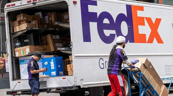A FedEx driver scans packages in San Francisco