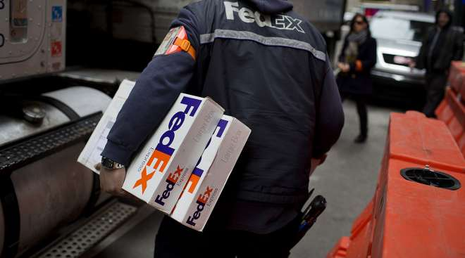 The driver for an independent contractor to FedEx Corp. delivers packages in Midtown Manhattan in New York.